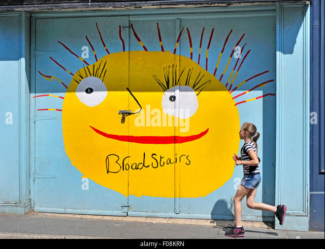 Broadstairs, Kent, England, UK. Young girl running past a painted shop in the high street - Stock-Bilder