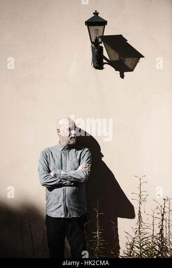 Serious and cool old man standing in front of wall. Sunshine and heavy shadow. Building exterior with copy space. - Stock-Bilder