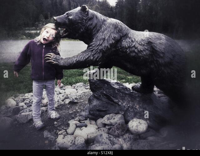 A surprised girl is 'bitten' by a grizzly bear. - Stock Image