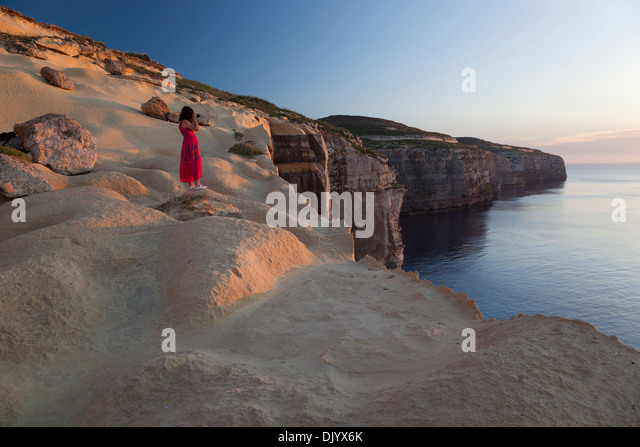 A woman taking pictures of the setting sun from atop the seacliffs at the northwesterly coast of Gozo. - Stock Image
