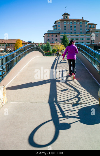 Tourists cross a bridge over Cheyenne Lake, The Broadmoor, historic luxury hotel and resort, Colorado Springs, Colorado, - Stock Image