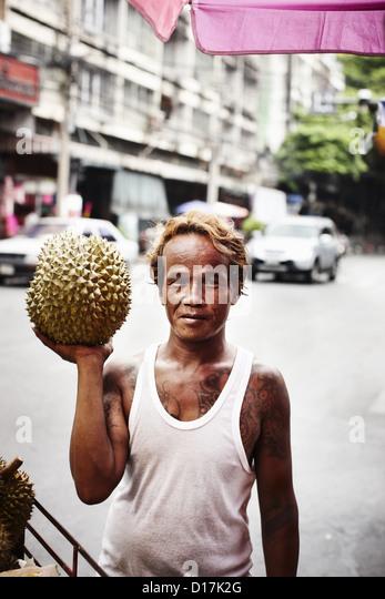 Man selling durian fruit on street - Stock Image