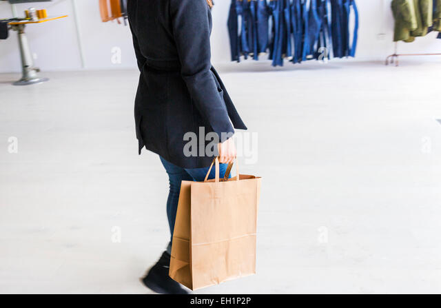 Low section of woman carrying shopping bag in factory - Stock Image