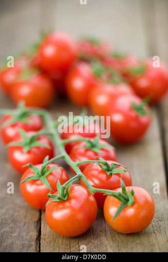 Close up of a string of vine-ripe cherry tomatoes on a rustic wooden tabletop. - Stock-Bilder