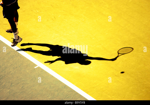 Shadow of tennis player serving - Stock Image