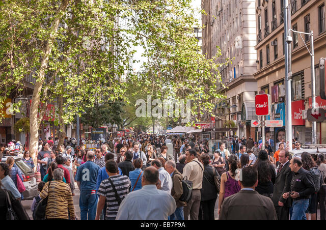 Santiago Chile, Paseo Ahumada. Crowds of people, shoppers, walking talking in the main shopping street of Santiago - Stock Image