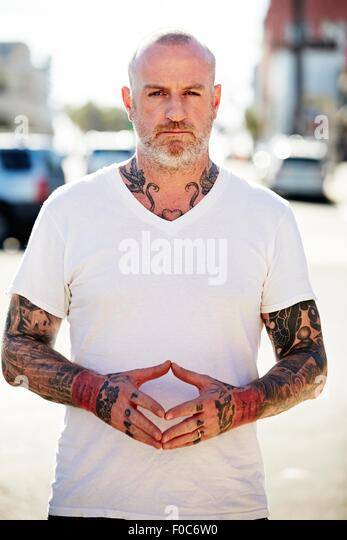 Mature man with tattoos on arms and neck - Stock-Bilder