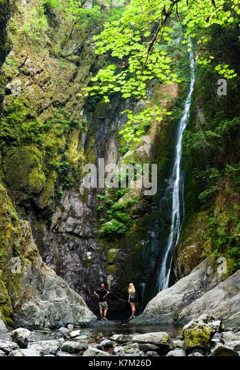 Couple at base of Niagara Falls - Goldstream Provincial Park - Victoria, Vancouver Island, British Columbia, Canada - Stock Image