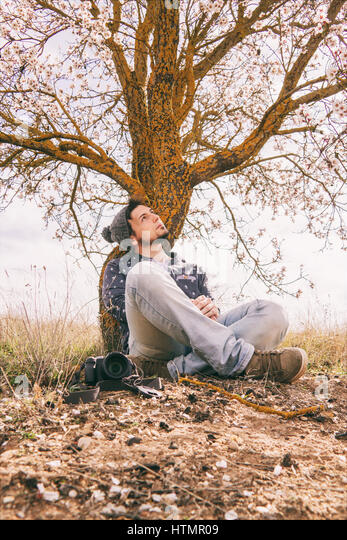 Young hipster man taking shots near a blossom tree in spring - Stock Image