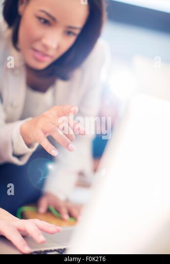 Focused businesswoman pointing at laptop - Stock-Bilder