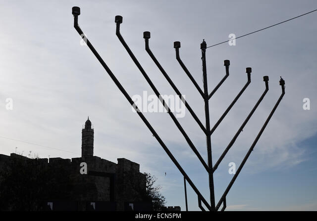 A 'chanukkiah', an eight-branched menorah or candelabrum, is set below the early Muslim period round tower, - Stock Image
