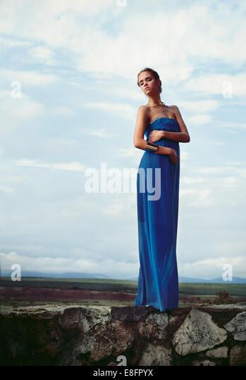 Woman wearing blue long dress standing on stone wall - Stock Image