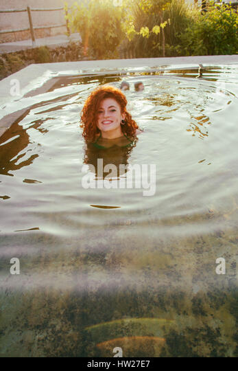 Young redhead woman enjoying a summer day in a natural pool - Stock Image