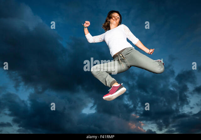 Young woman, 19 years old, jumping, in mid-air, against the evening sky - Stock-Bilder