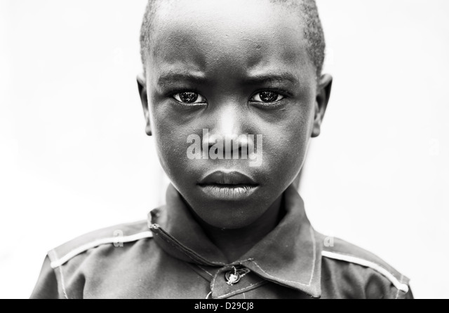 An African child looking intensely into the camera. - Stock Image