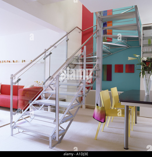 Metal stairs separating lounge and dining room - Stock Image