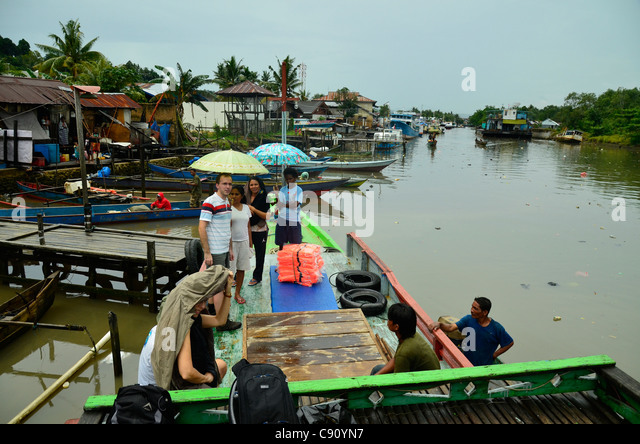 Tourists on fishing boat, Sorong, West Papua in the Pacific Ocean, Indonesia. - Stock Image