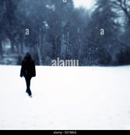 girl walking in snow - Stock Image