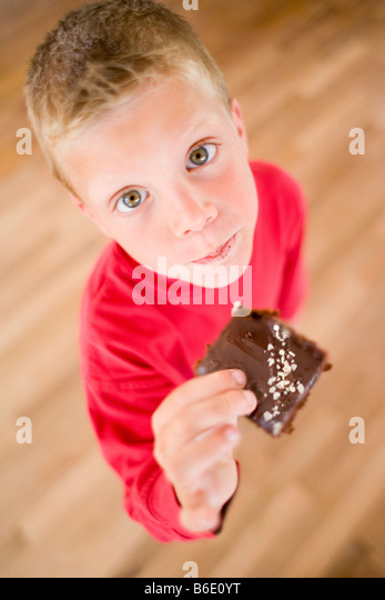 Boy eating chocolate cake. Sweet foods contain high amounts of sugar and fat and eating too much can lead to childhood - Stock Image