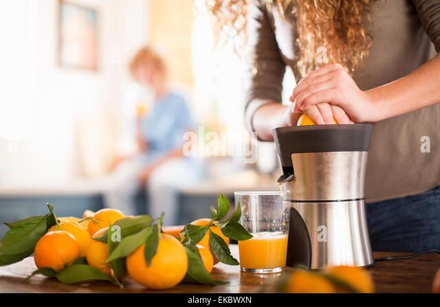 Teenage girl juicing orange in kitchen - Stock Image