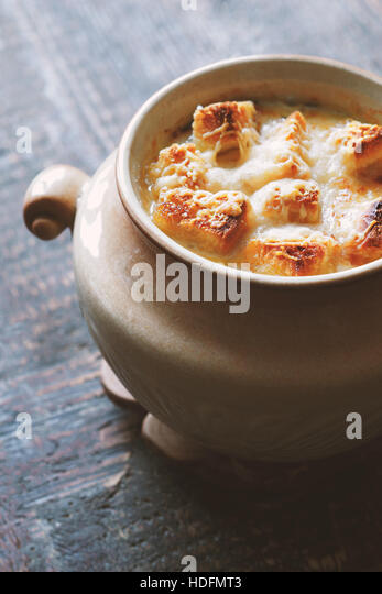 Onion soup in the ceramic pot on the wooden table vertical - Stock Image