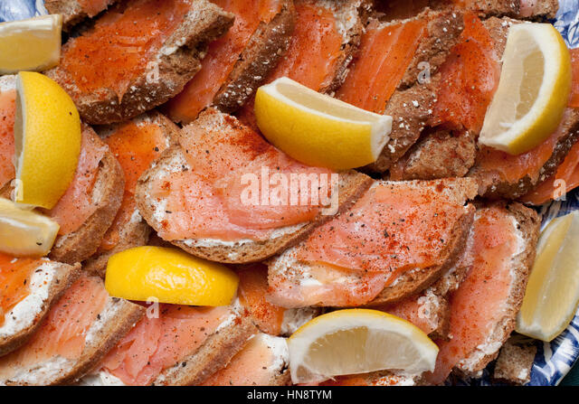 Smoked salmon on brown braed with wedges of lemon - Stock Image