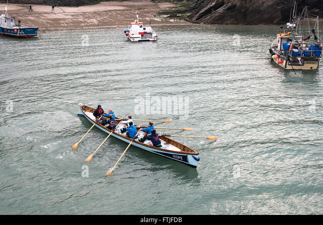 Hope, a traditional Cornish racing gig is rowed out of Newquay Harbour by its all female crew. - Stock Image