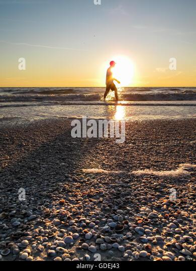 Man walking along beach at sunset, Florida, America, USA - Stock Image