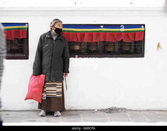 A woman stands outside a room of prayer wheels in the Boudhanath Pagoda in Kathmandu, Nepal. - Stock Image