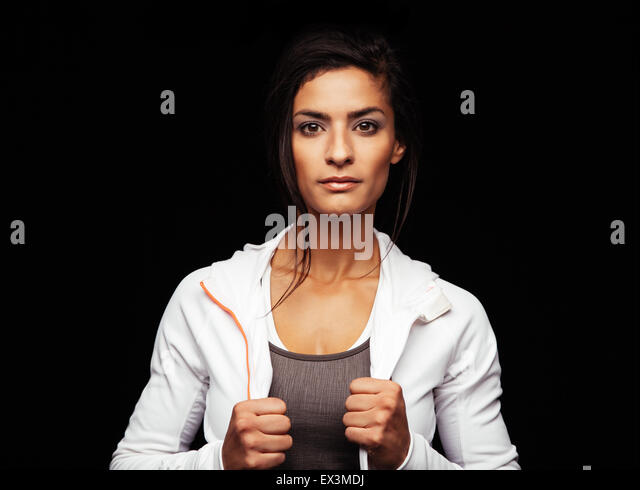 Shot of young fitness model posing in studio. Healthy young woman in sportswear standing against black background. - Stock Image
