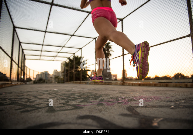 Legs of female jogger running on walkway - Stock Image