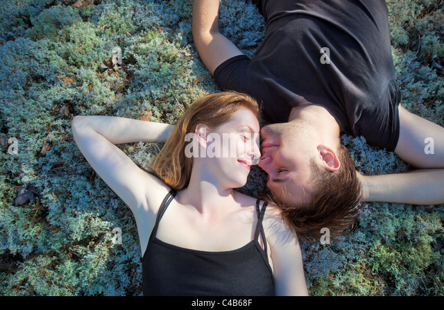 Young couple resting on grass in forest. - Stock Image