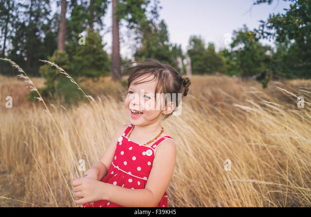 Portrait of a girl standing in a field, laughing - Stock Image