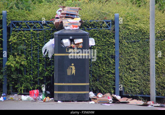 A litter bin overflows with rubbish on a street in Sheffield, South Yorkshire, England UK - Stock Image