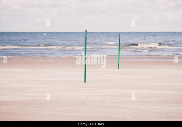 Strong wind on the sandy beach of the Baltic Sea with a pair of green pillars volleyball court in the autumn on - Stock Image