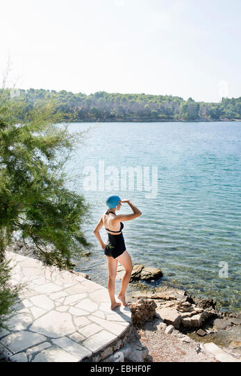 Rear view of young woman wearing swimming costume gazing out to sea, Milna, Brac, Croatia - Stock Image