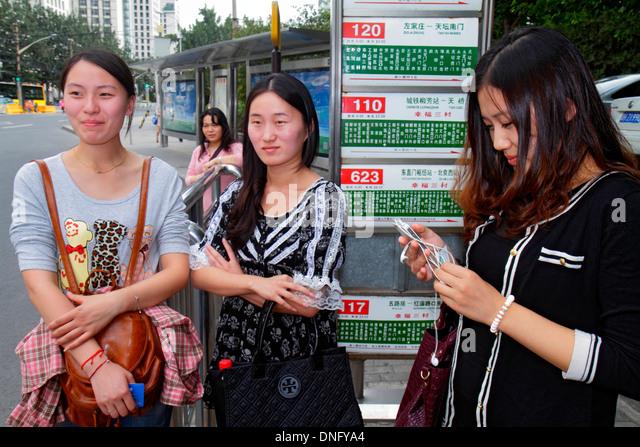 China Beijing Dongzhimen bus stop public transportation Asian woman friends waiting Chinese characters hànzì - Stock Image