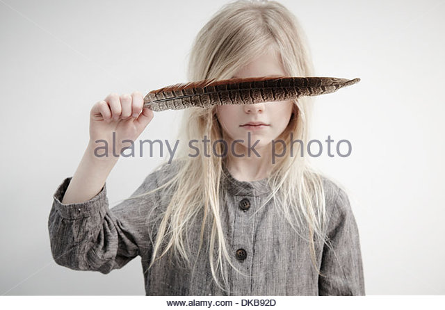 Portrait of girl holding feather over eyes - Stock Image