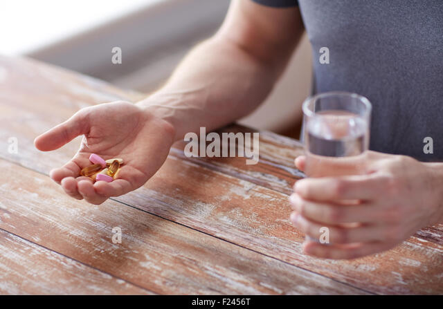close up of male hands holding pills and water - Stock Image