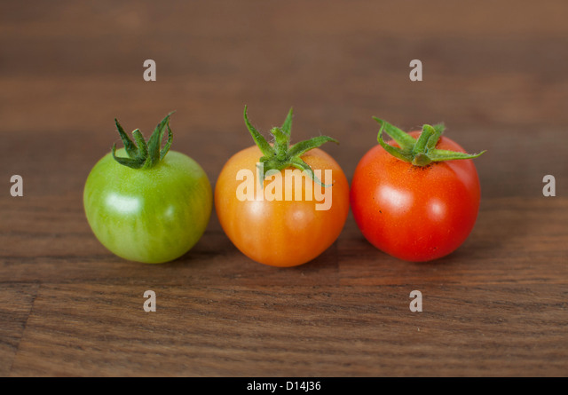Different colored tomatoes on table - Stock Image