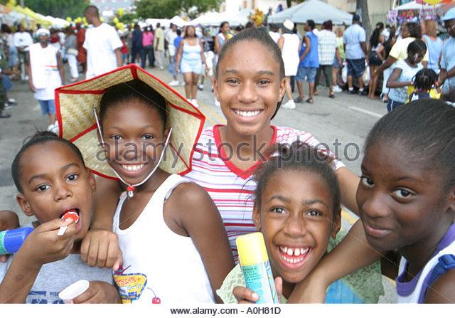 Coconut Grove Florida Grand Avenue Bahamas Goombay Festival Black girls laughing happy - Stock Image