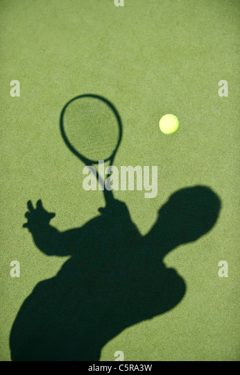 A tennis player silhouette returns the ball. - Stock Image