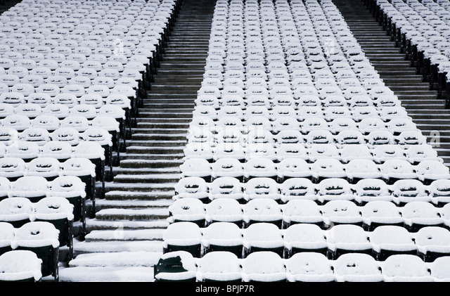 Empty stadium seats covered in snow - Stock Image