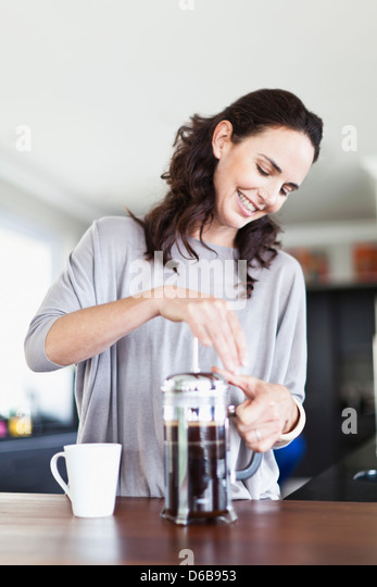 Woman making french press coffee - Stock Image