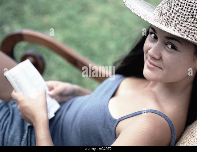 Young woman sitting outdoors in a chair looking at the camera holding a book - Stock Image