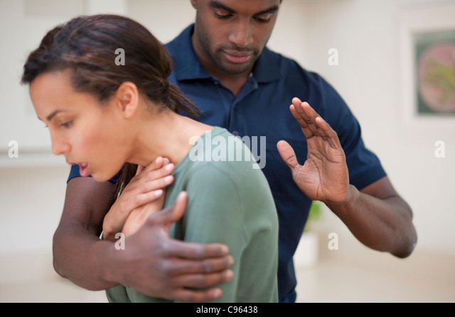 Woman choking. The man is trying to dislodge the foreign object by hitting her between the shoulder blades. - Stock Image