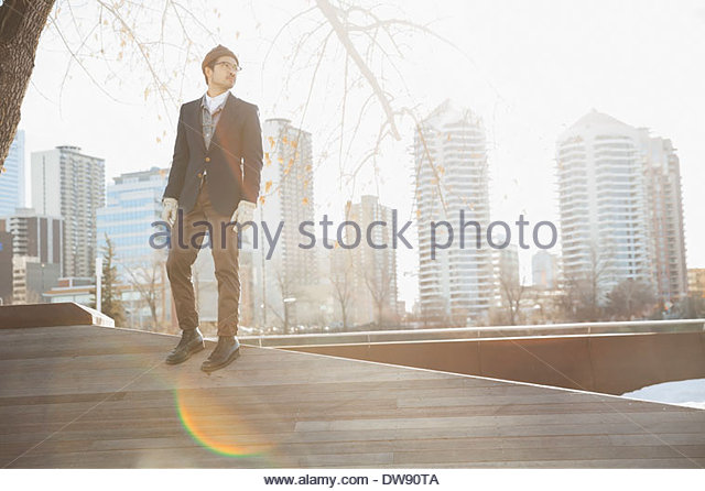 Man standing on wooden slope against cityscape - Stock-Bilder