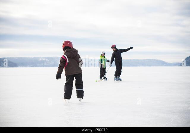 Sweden, Vastergotland, Lerum, Lake Aspen, Mom playing ice hockey with her two children (6-7, 8-9) on lake - Stock Image