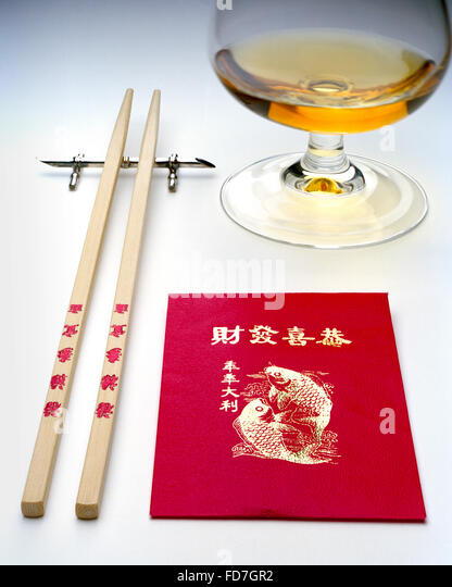Kung Hei Fat Choi in gold characters on red lucky money envelope with chopsticks and brandy glass - Stock Image