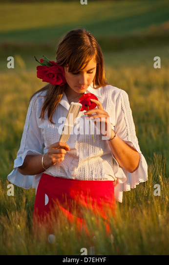 Field of wild Poppies with Spanish girl in traditional dress  Spring flowers poppy Fiesta Ferria, wild flowers Andalucia - Stock Image
